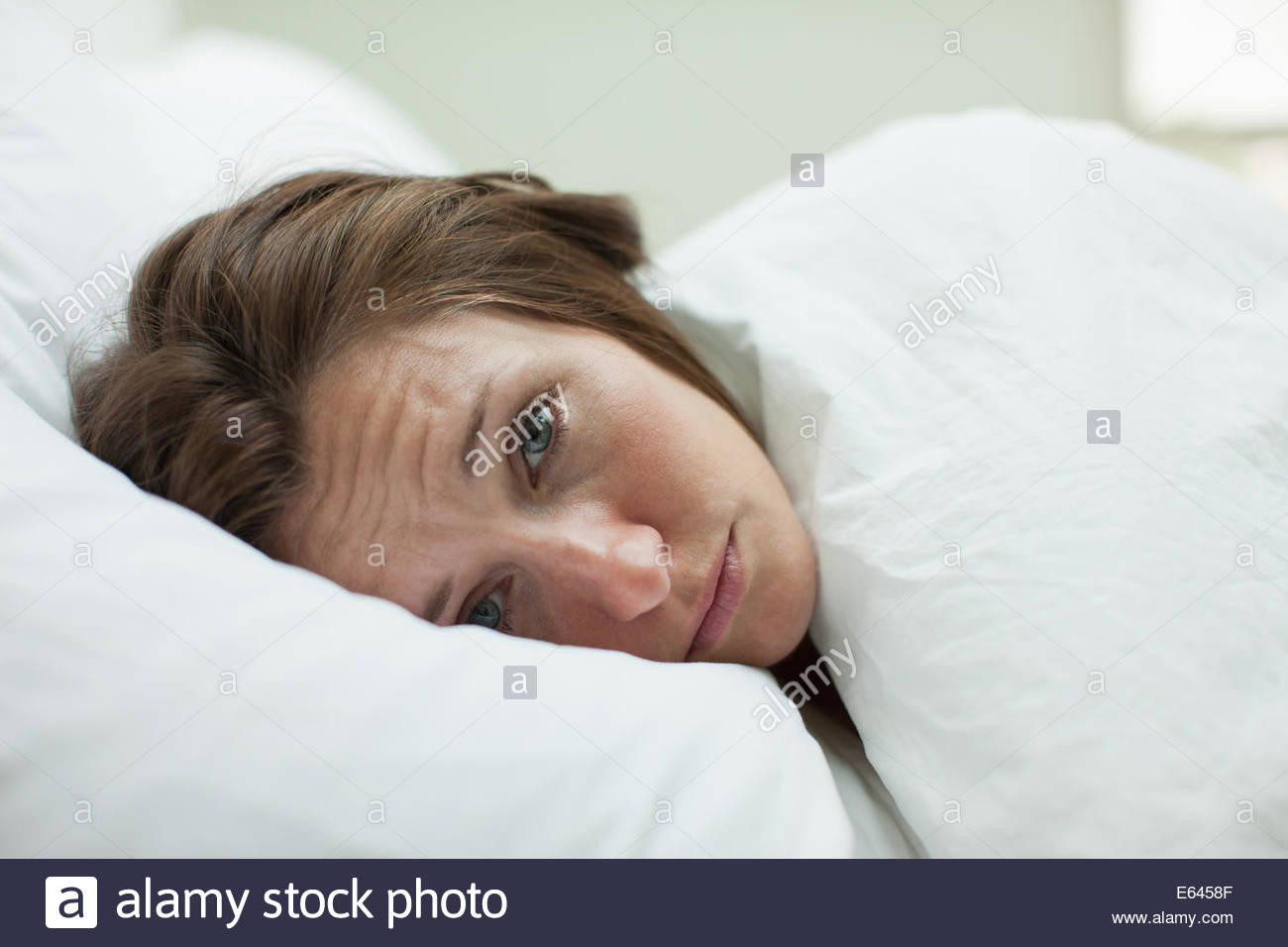 Sick woman laying in bed sous couverture Photo Stock