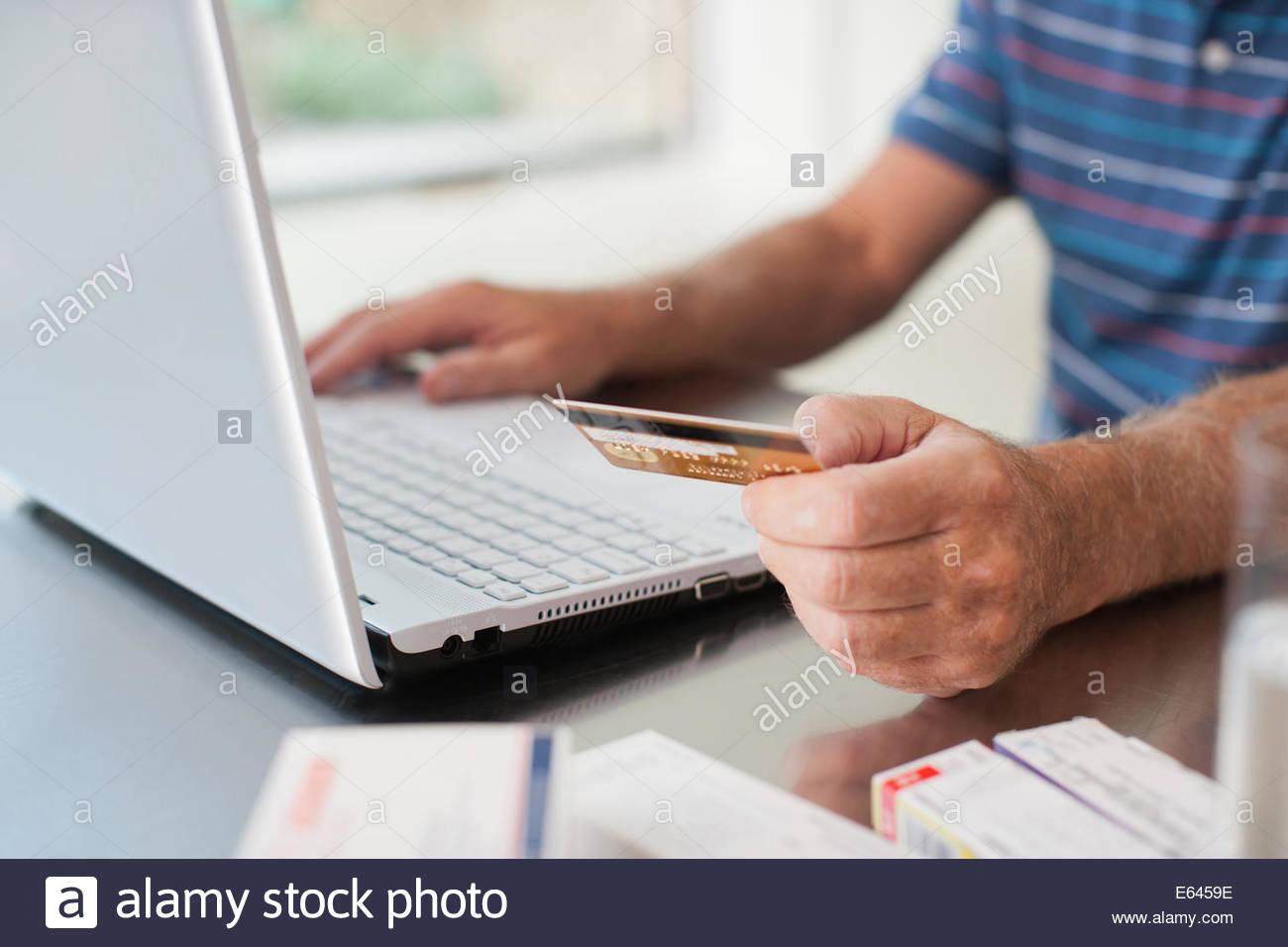 Close up of man en utilisant une carte de crédit pour acheter des produits dérivés en ligne Photo Stock