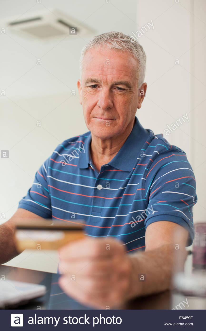 L'homme en utilisant une carte de crédit pour acheter des produits dérivés en ligne Photo Stock