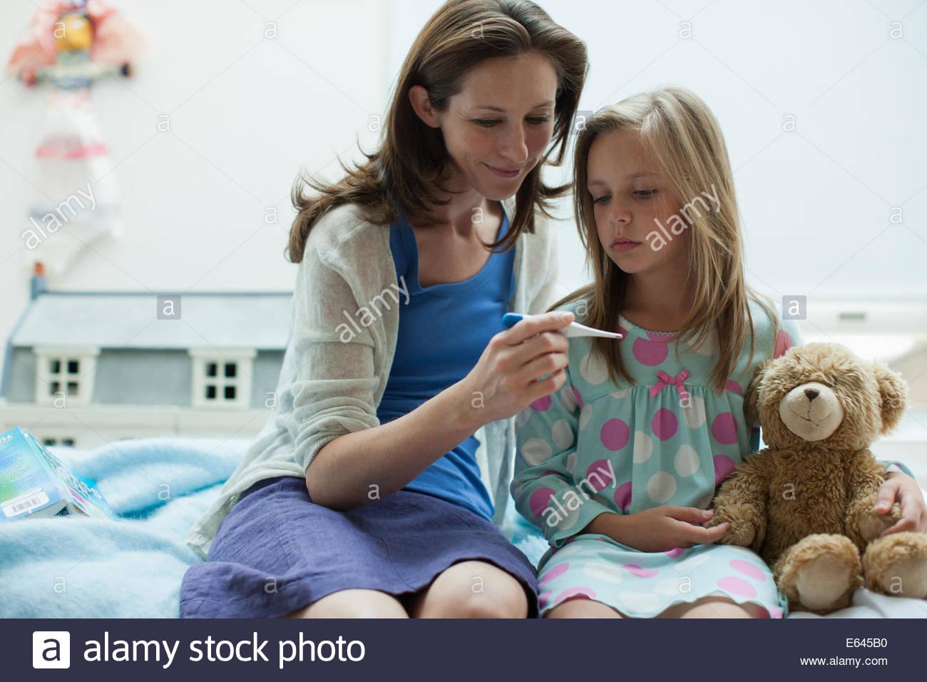 Contrôle de la température de la mère de la fille avec un thermomètre digital Photo Stock