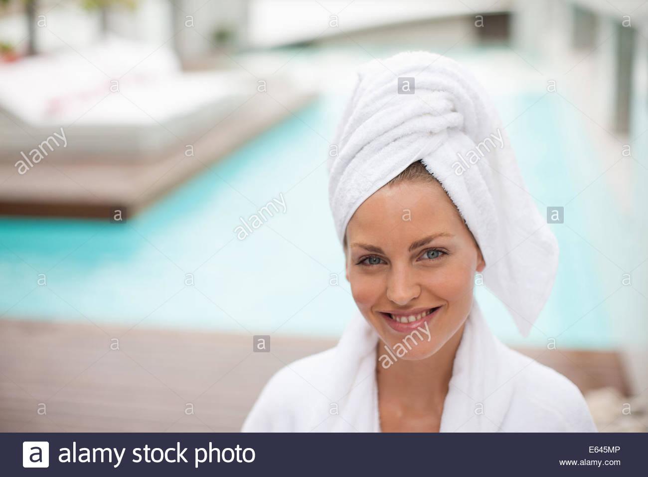 Femme avec cheveux enveloppés dans une serviette au bord de la piscine Photo Stock