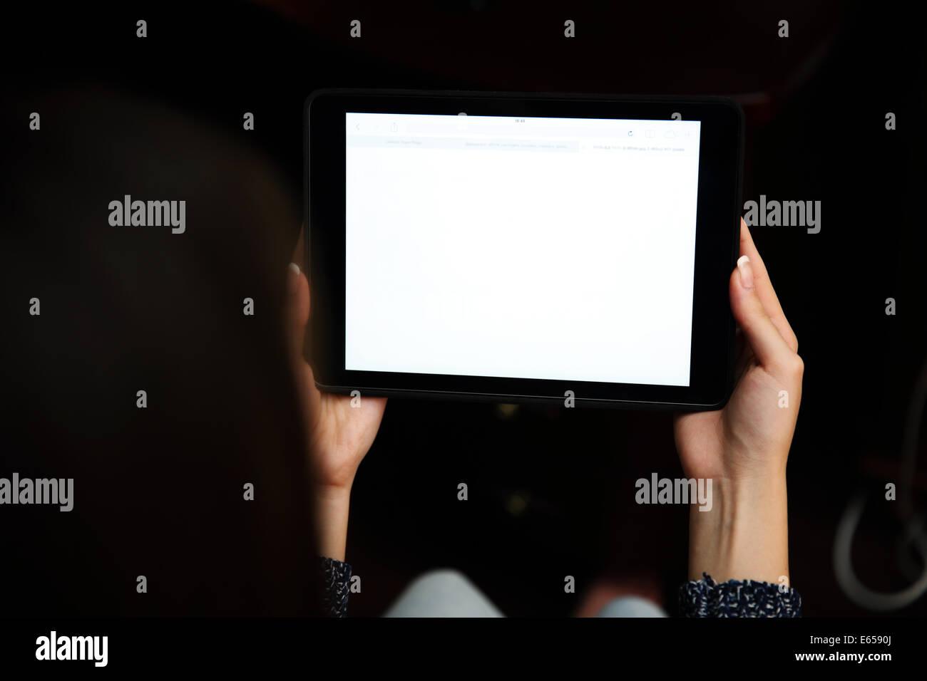 Vue arrière portrait of a woman holding tablet computer Photo Stock