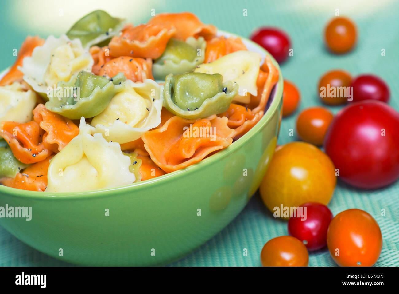 Tortellini, tricolore, pâtes de couleur orange vert dans un bol Photo Stock