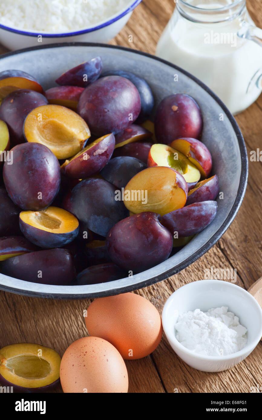 Ingrédients pour cuire un gâteau aux prunes sur une table en bois rustique Photo Stock
