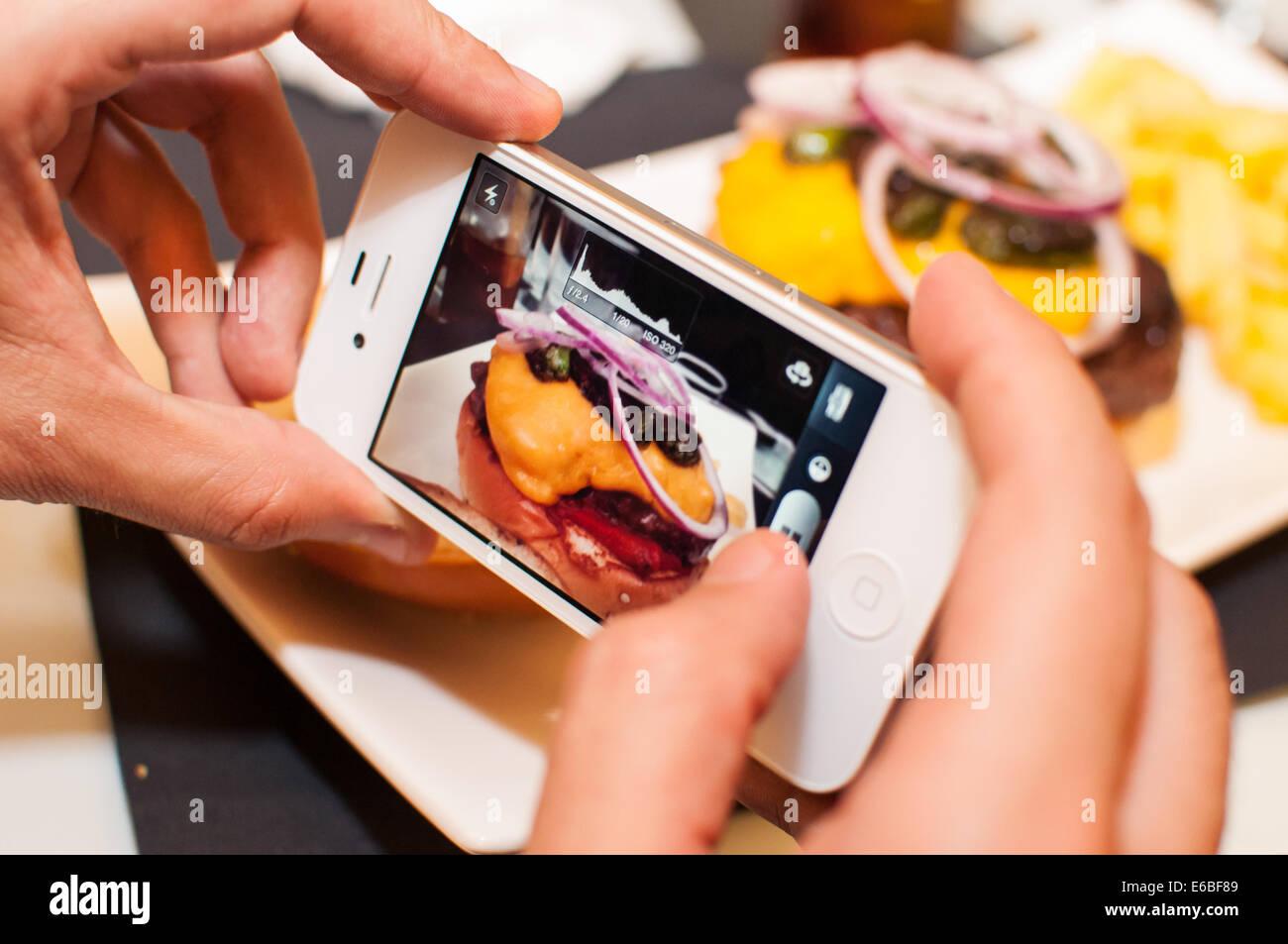 Photographie d'un hamburger au moyen d'un smartphone Photo Stock