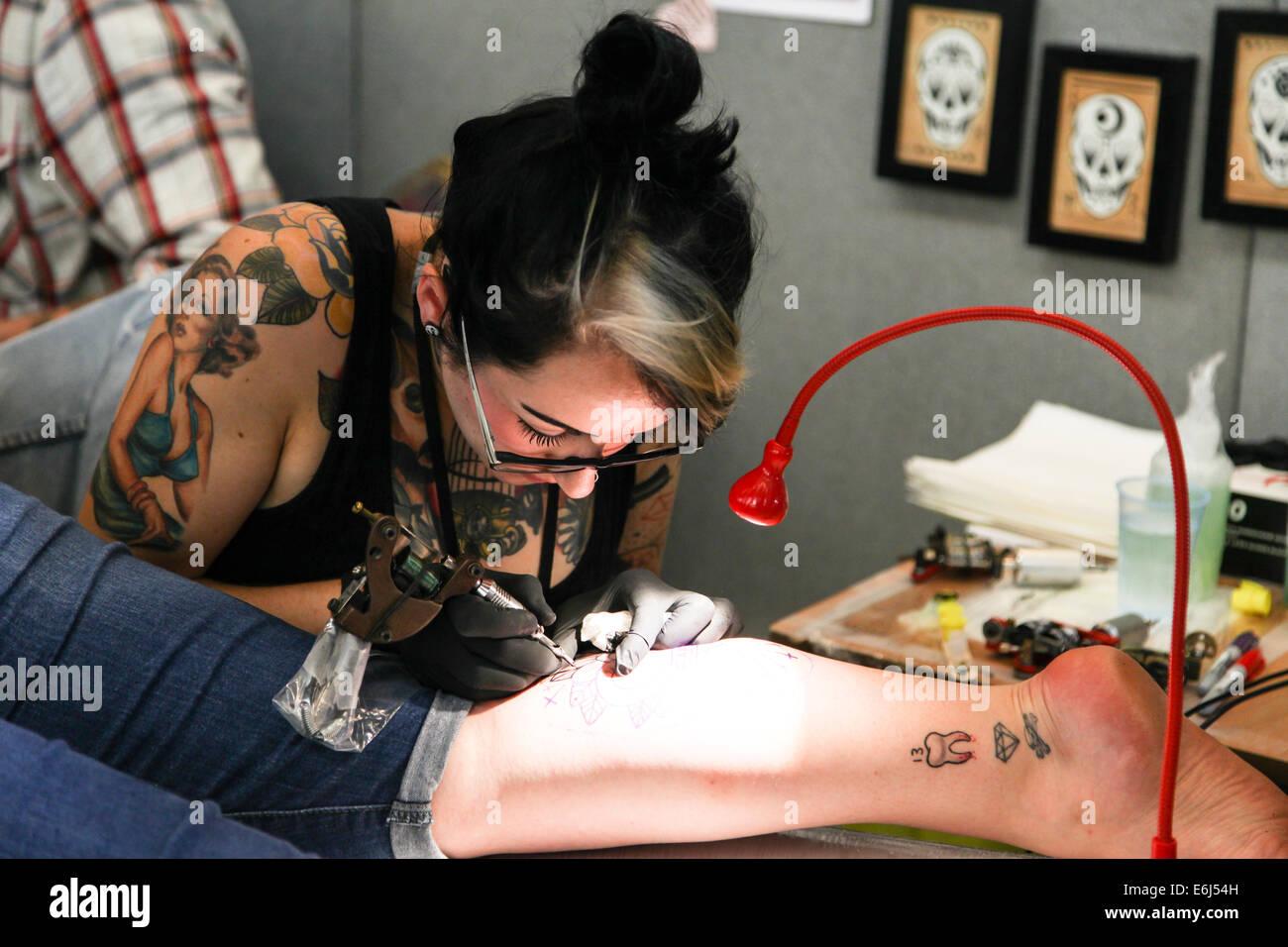Femme au travail tatoueur le tatouage d'une jambe à la Norwich Festival body art Photo Stock