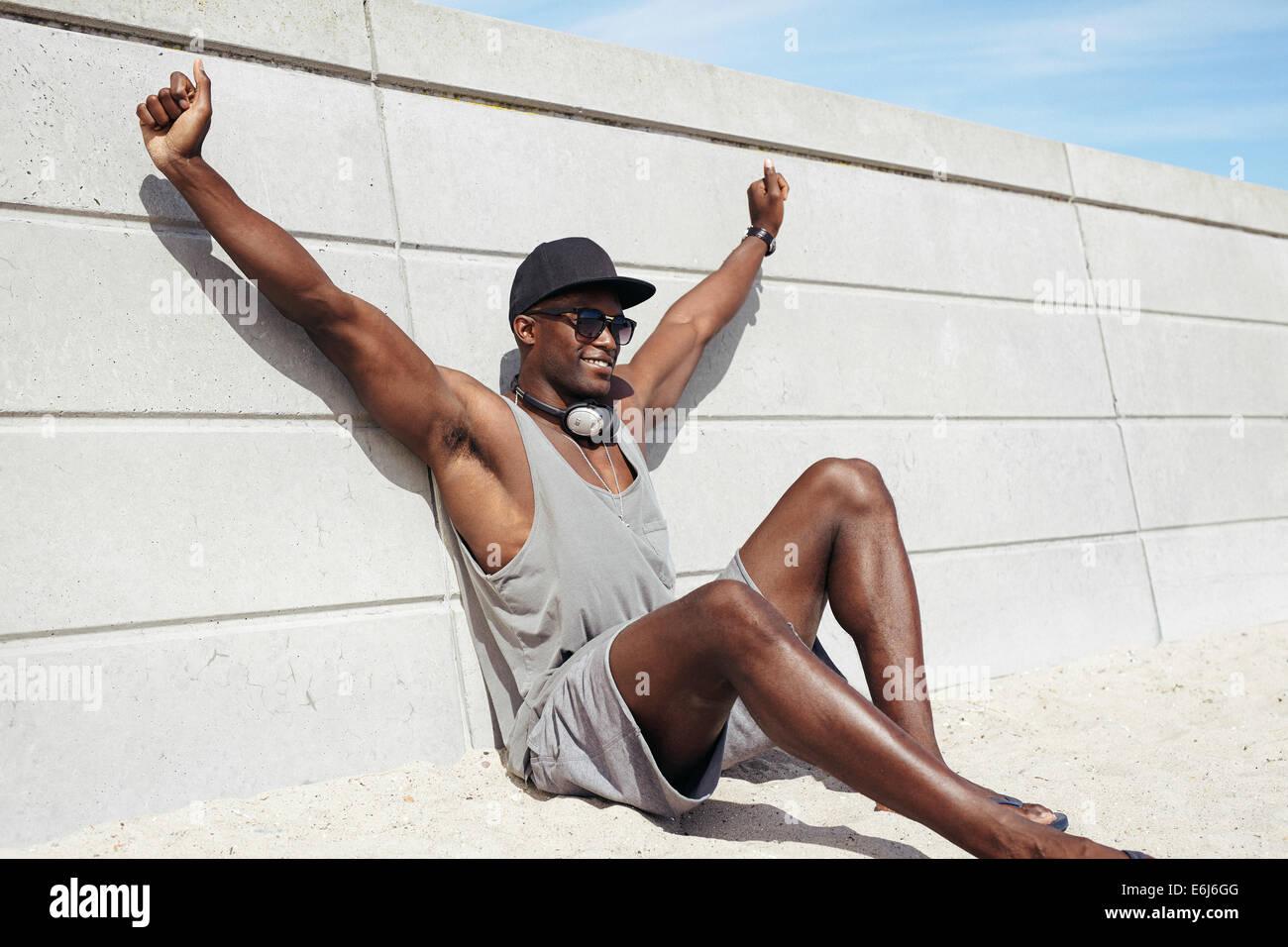 Jeune homme musclé assis par un mur s'étendant ses mains en souriant. Modèle masculin africain sur la plage. Banque D'Images
