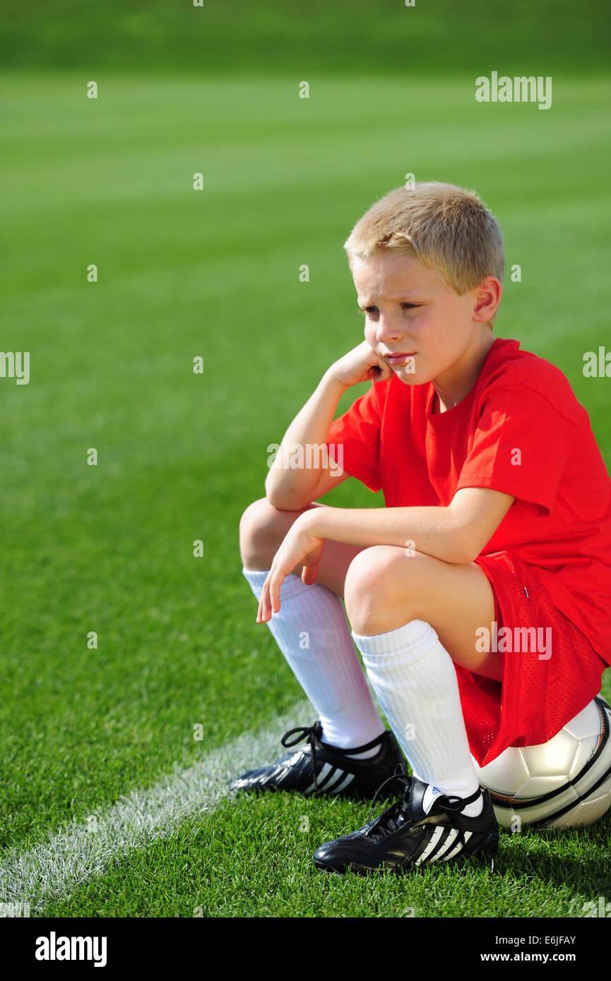 Boy 9 10 11 jouer au football futbol soccer sur terrain herbeux n'obtiennent pas de champ à jouer Photo Stock