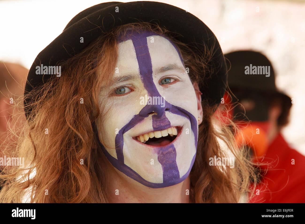 Souriante, aux cheveux longs, teenage boy - visage peint avec symbole de la CND. Photo Stock