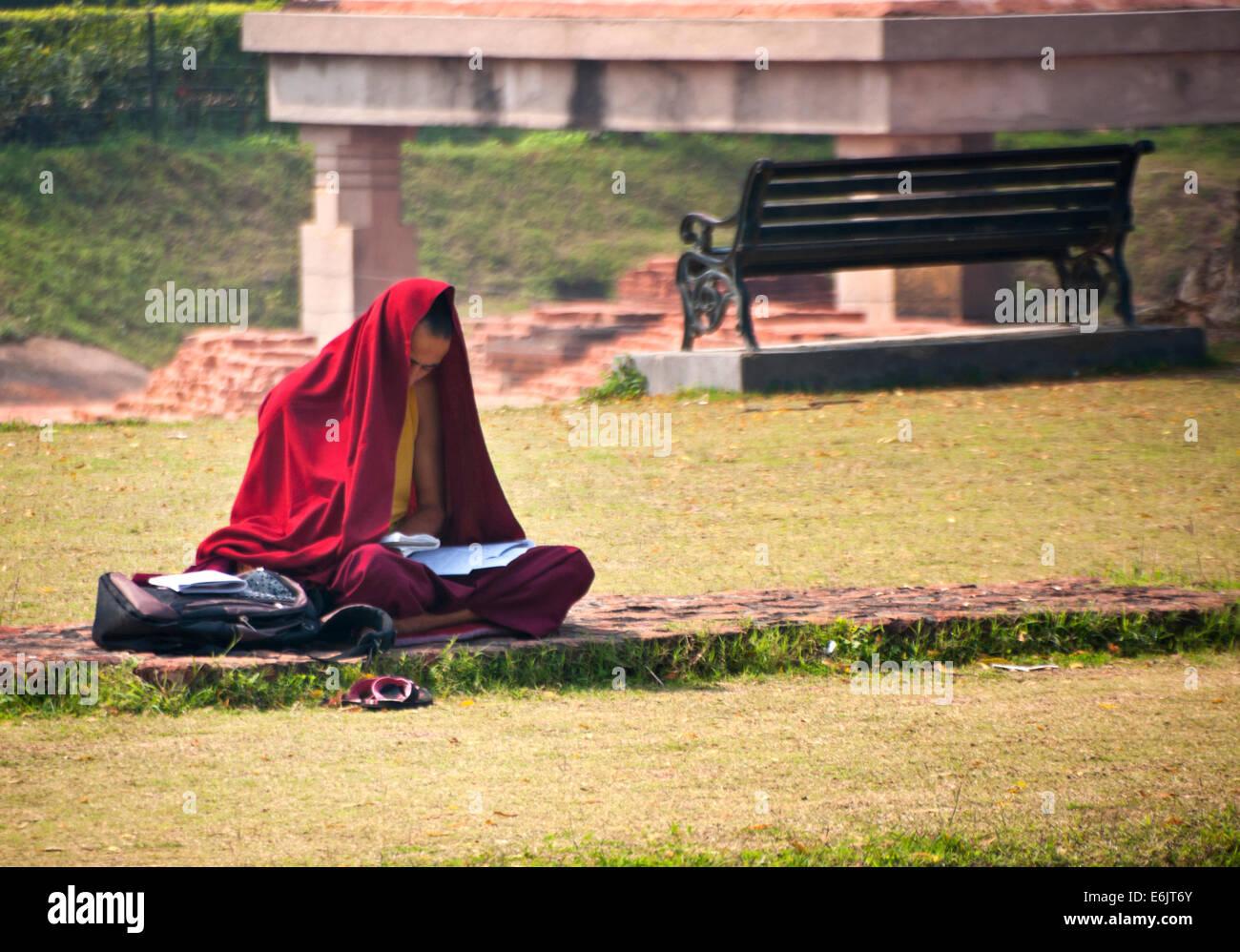 Jeune moine avec sa tête et son corps en partie couverte par une feuille de tissu rouge, sitting cross legged Photo Stock