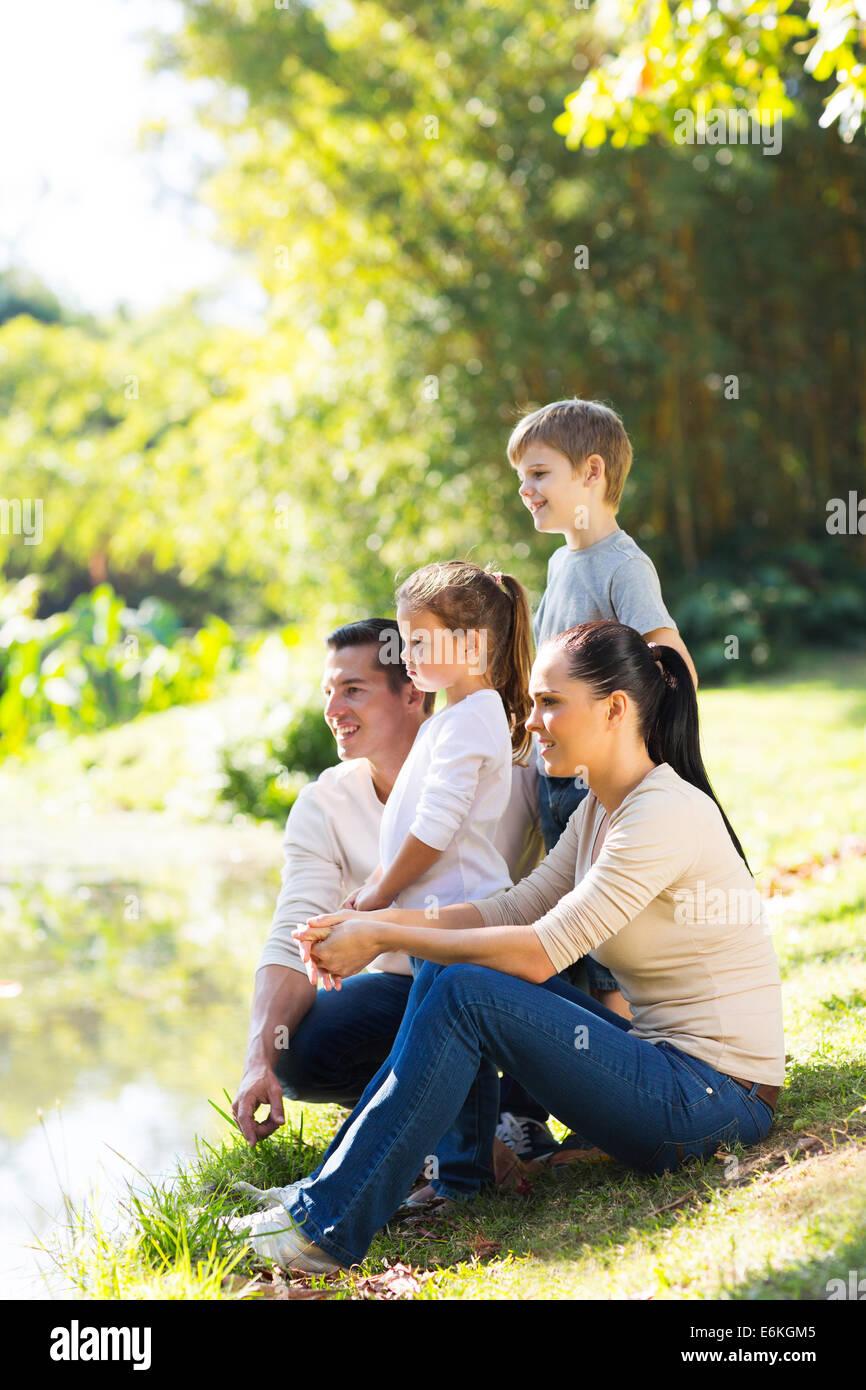 Famille heureuse de quatre par l'étang bénéficiant d'une journée Photo Stock