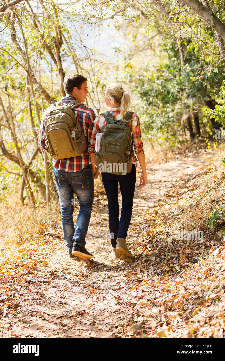 Happy young couple walking in autumn forest Photo Stock