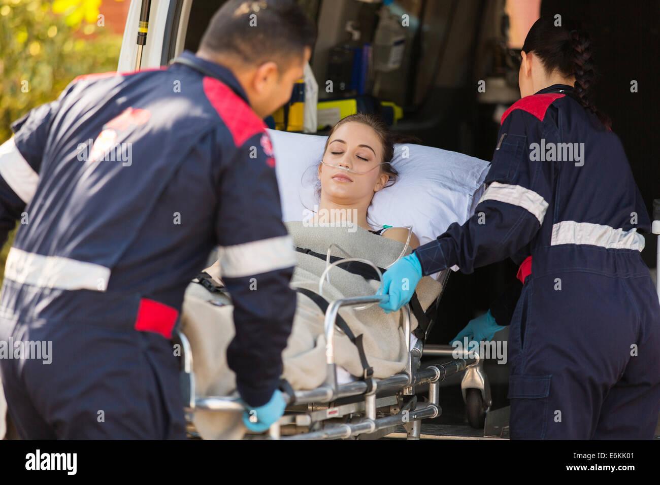 Les ambulanciers prenant patient inconscient dans une ambulance Banque D'Images