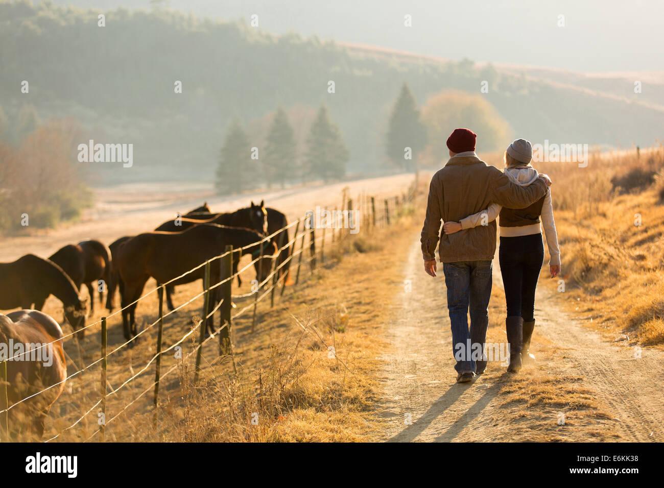 Vue arrière du jeune couple walking in farm road Photo Stock