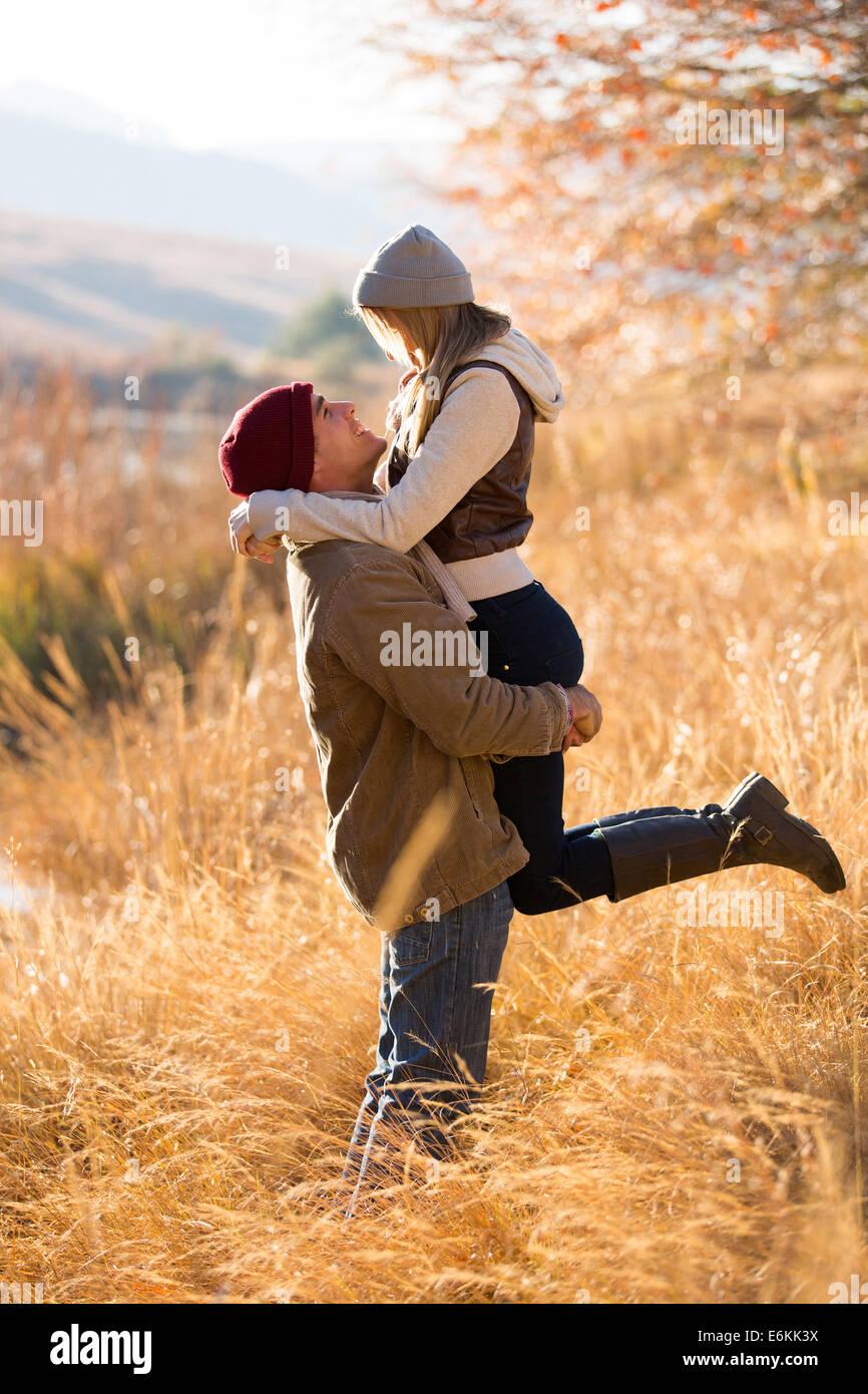 Jeune homme espiègle chercher sa petite amie par le lac à l'automne Photo Stock