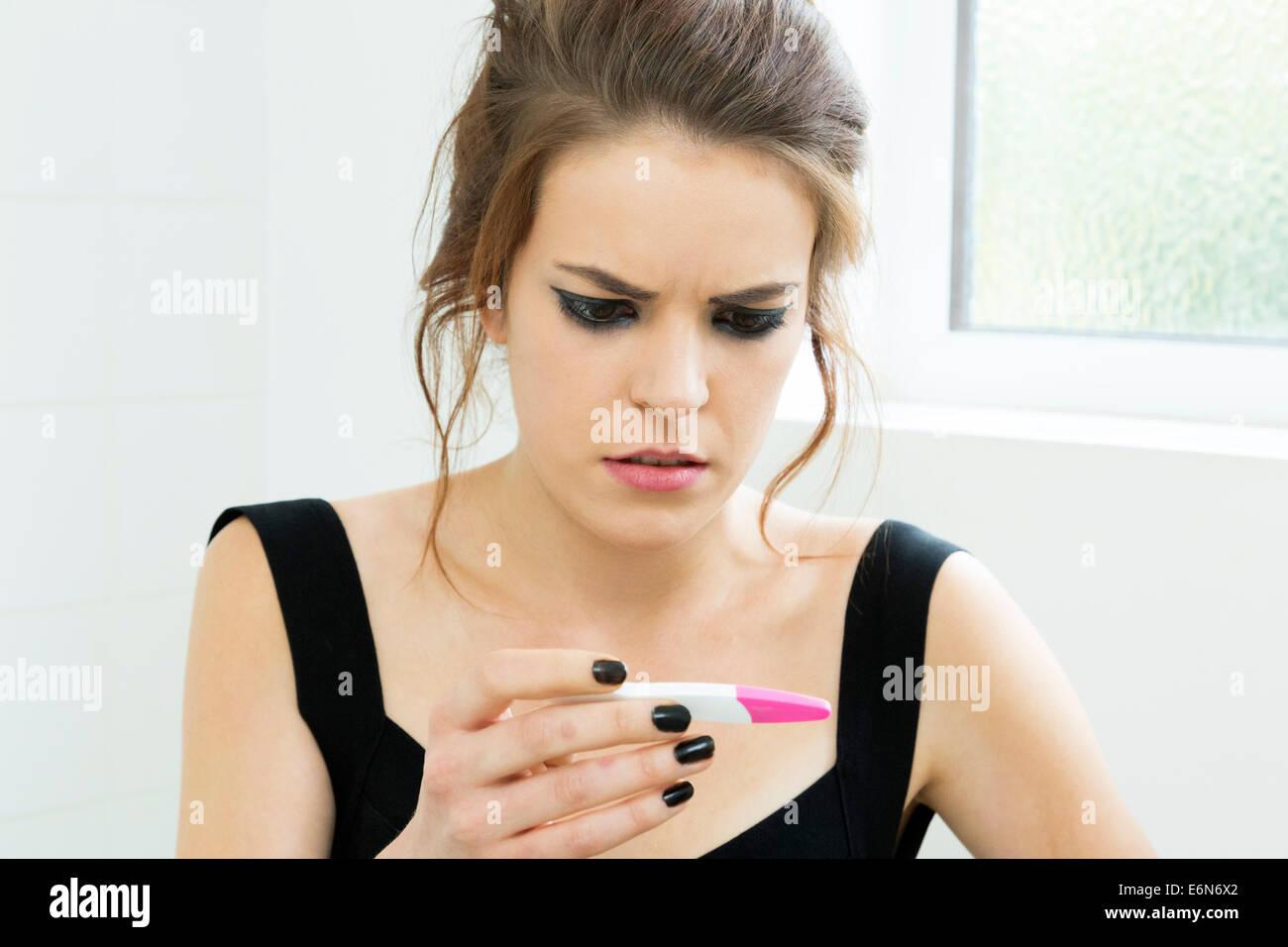 Femme inquiète en utilisant un test de grossesse Photo Stock