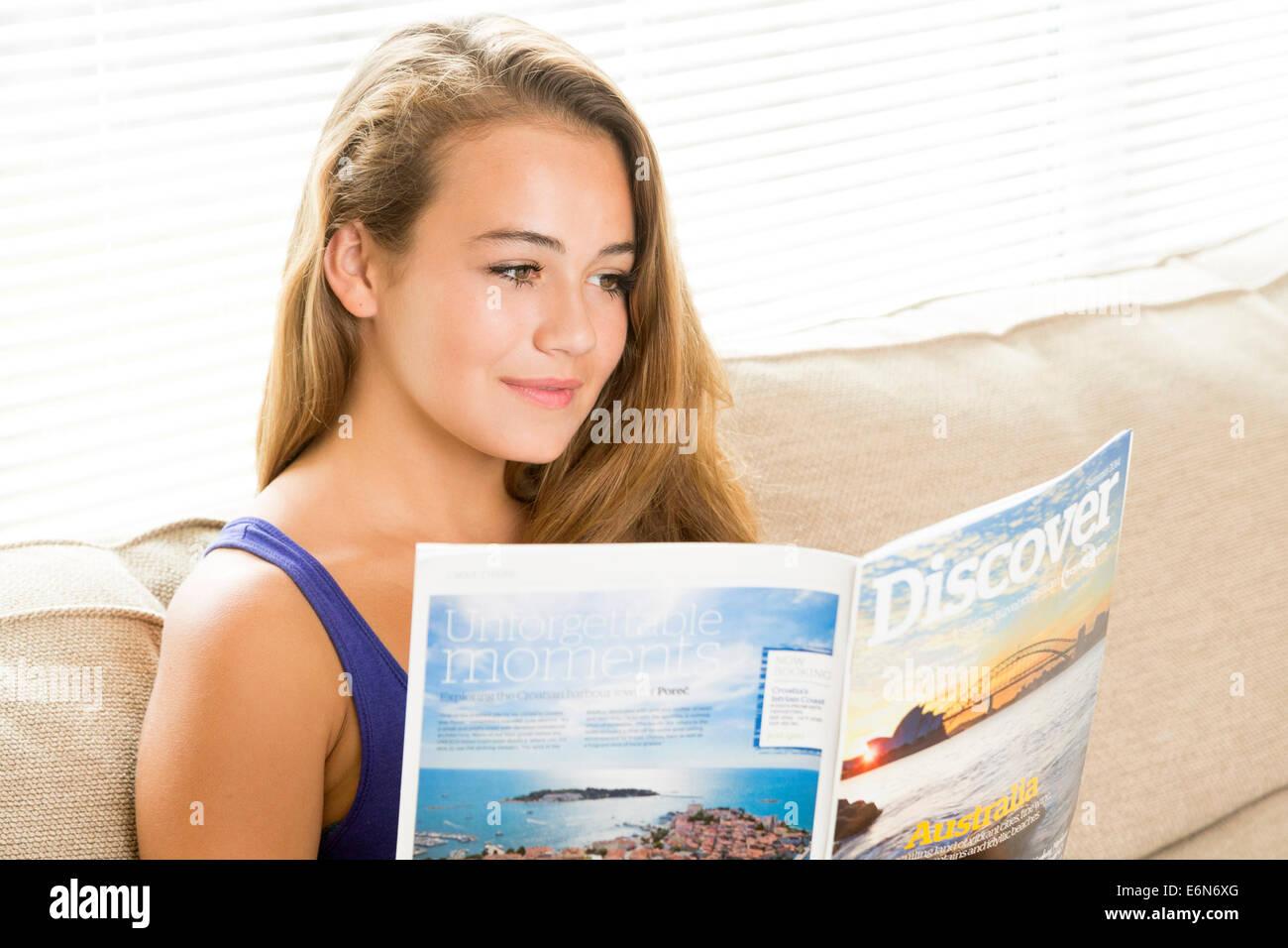 Young woman reading maison de vacances / vacation brochure Photo Stock