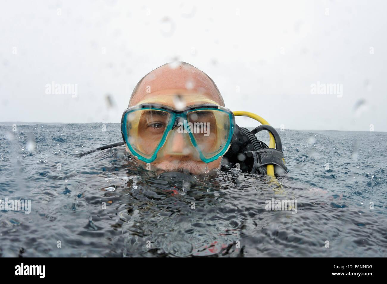 Portrait de plongeur autonome sous la pluie à la surface de l'eau Photo Stock