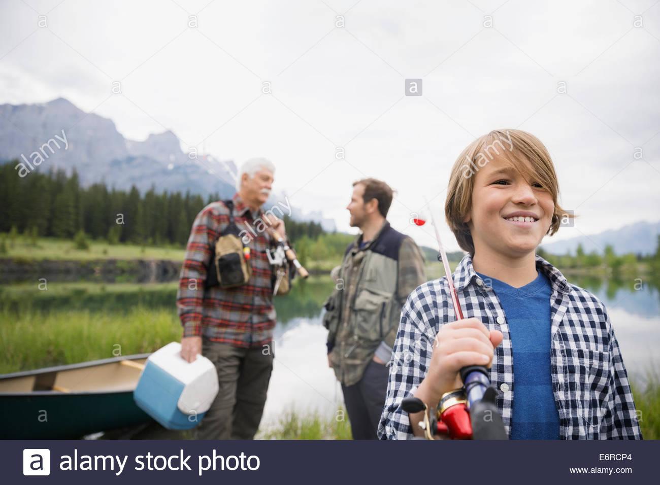 Trois générations d'hommes se tenant debout par still lake Photo Stock