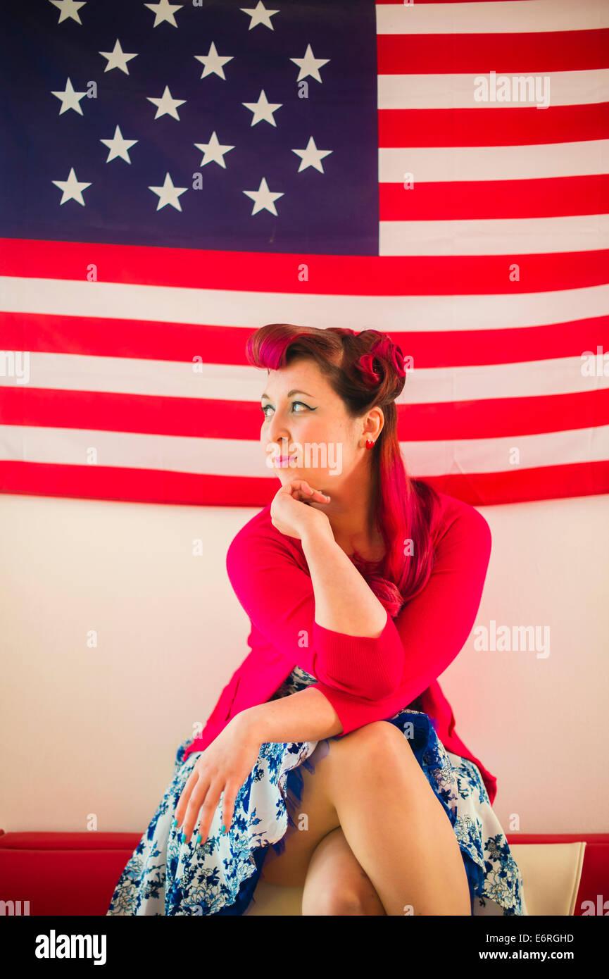 Une femme portant des vêtements rétro style années 50 assis devant un drapeau USA stars and stripes Photo Stock