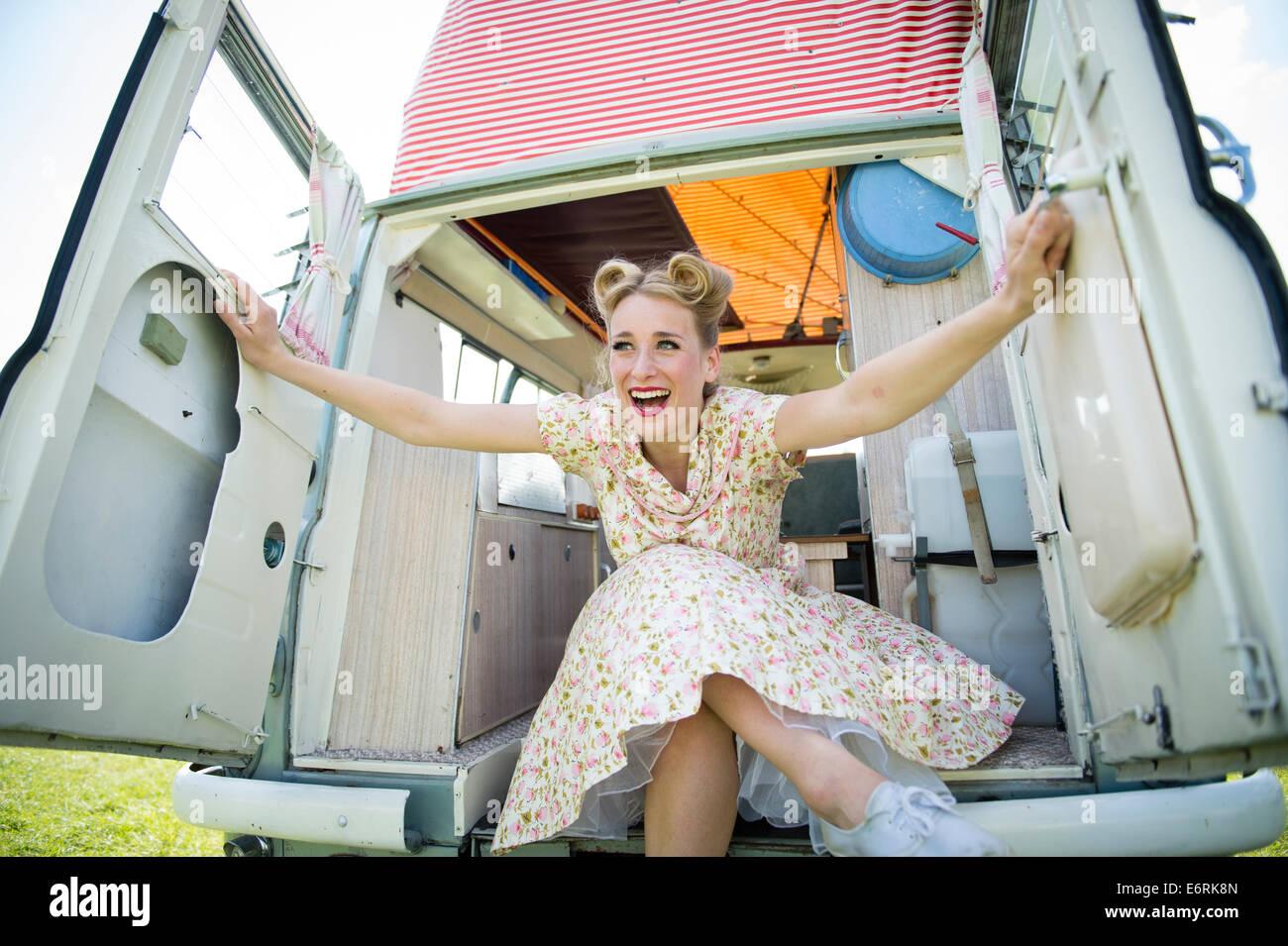 Une femme vêtue de retro 50's American style robe robe d'été femme au foyer assis posant Photo Stock