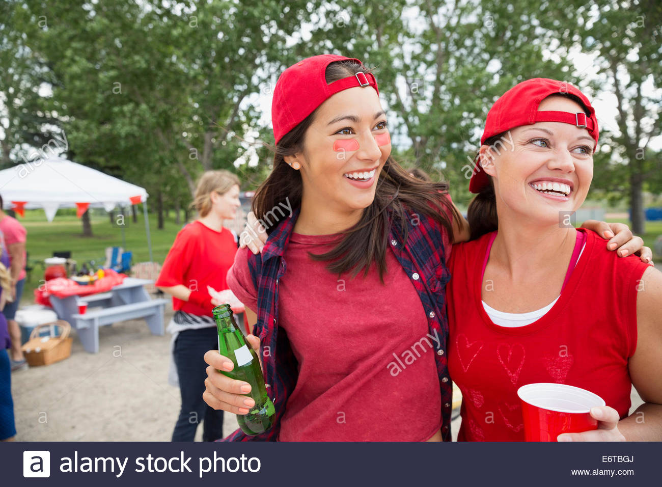 Women smiling together at barbecue in field Photo Stock