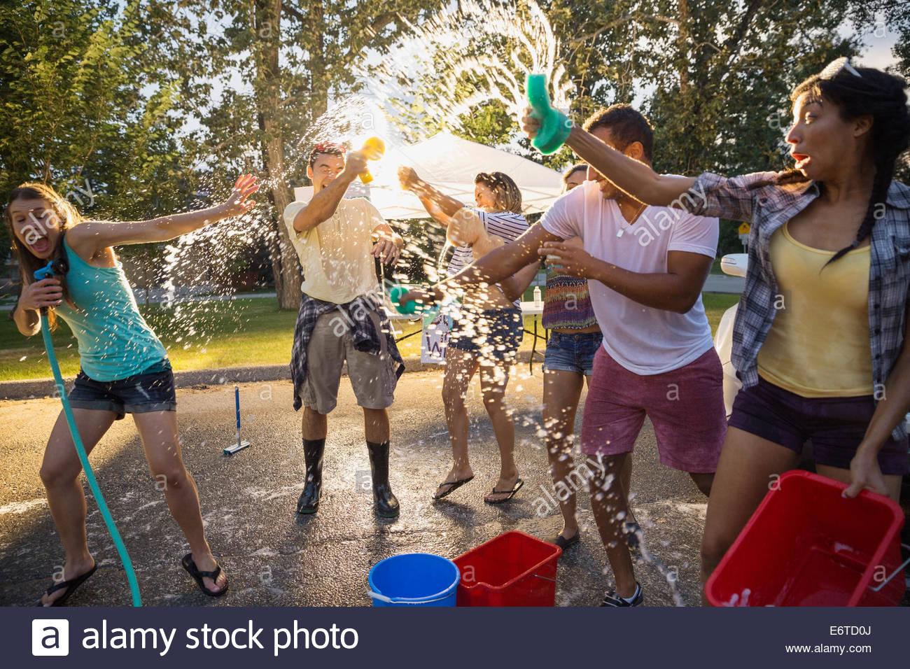 Amis espiègles à éclabousser la charité lavage de voiture Photo Stock