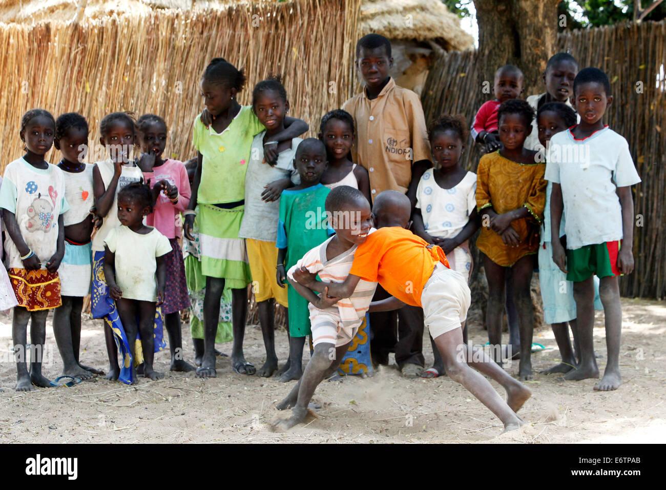 Les enfants effectuer un match de lutte. La lutte est le sport national. Sénégal, Afrique Photo Stock