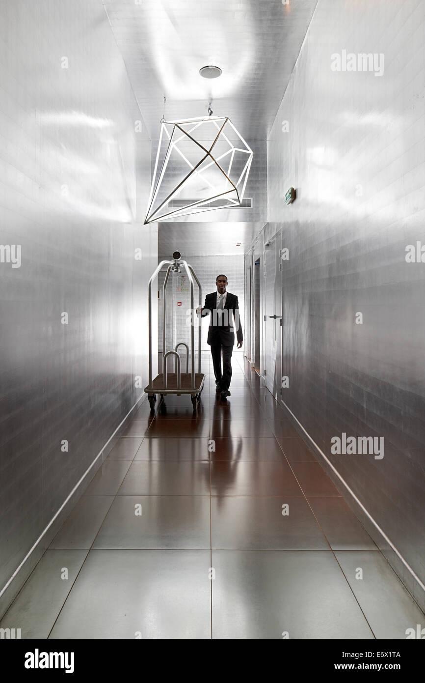 Commis d'hôtel dans le couloir avec des murs couverts d'argent dans l'aluminium, l'Hôtel Photo Stock