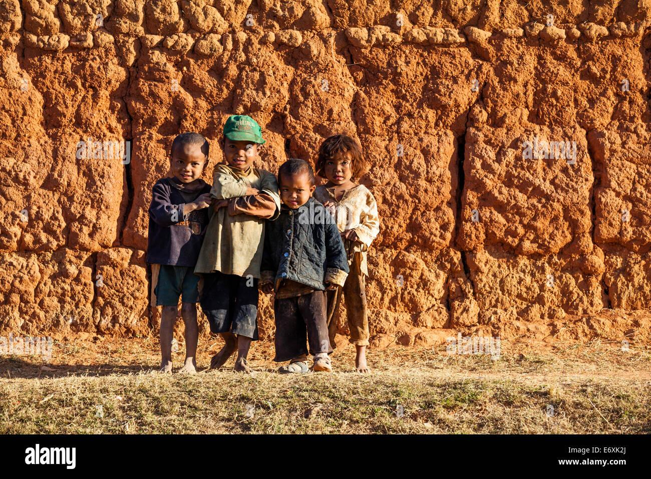 Les enfants debout devant un mur d'argile au sud d'Antananarivo, peuple Merina, highlands, Madagascar, Afrique Photo Stock