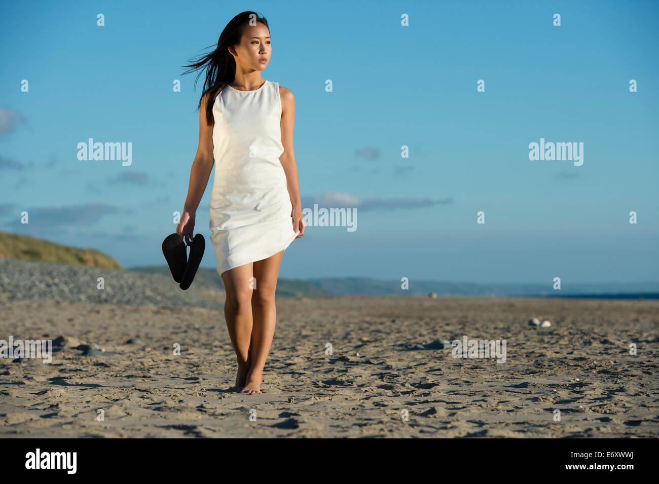 Un jeune chinois asiatique ethnique femme fille vêtue d'une robe blanche tenant ses chaussures marcher seule le long d'une plage de sable fin de l'été UK Banque D'Images