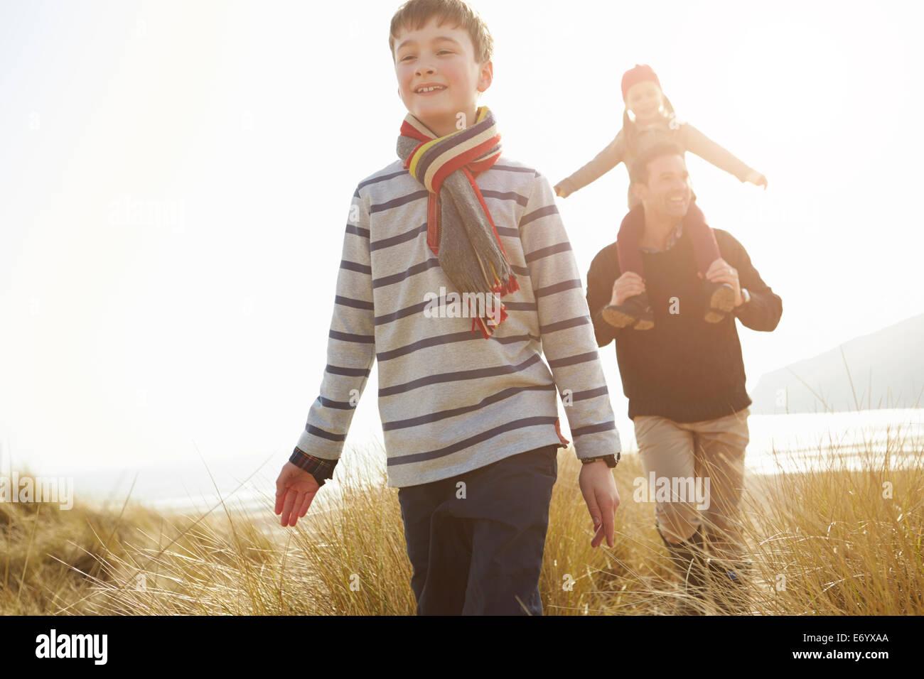 Le père et les enfants marche à travers les dunes sur la plage d'hiverBanque D'Images