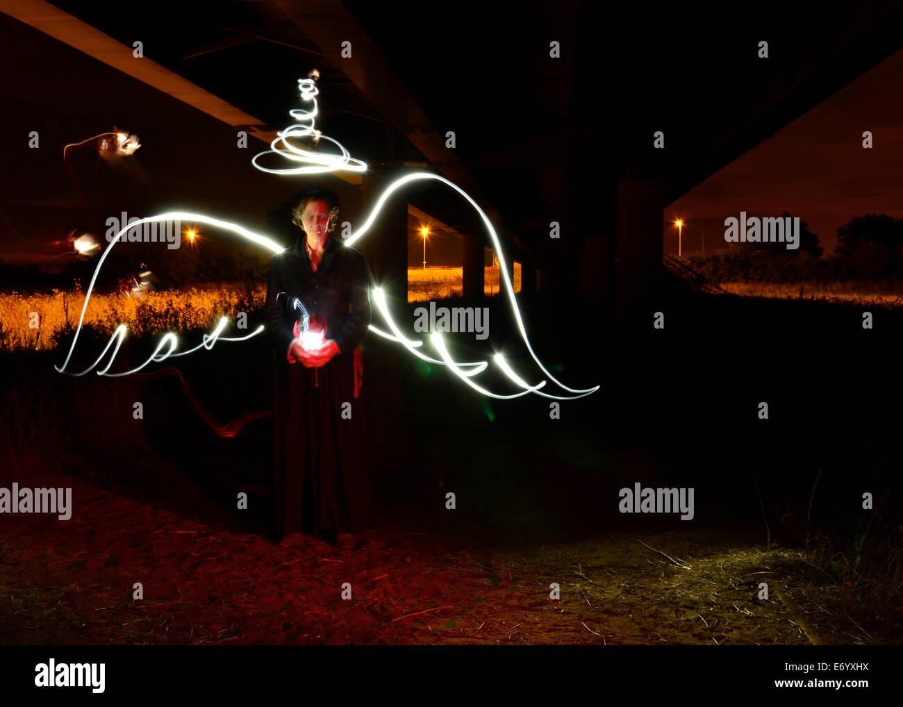 Un ange surréaliste, créé avec la lumière de la peinture, les ailes et l'auréole dans, aucun flash une lanterne et vélo lumières pour créer un éclairage naturel Banque D'Images