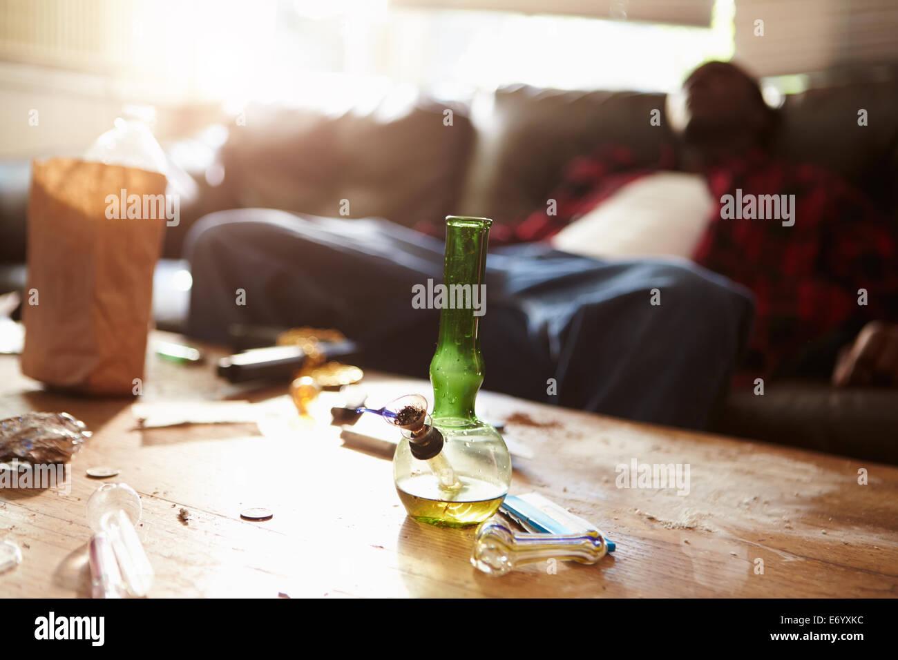L'homme affalé sur le canapé avec l'attirail de drogue en premier plan Photo Stock