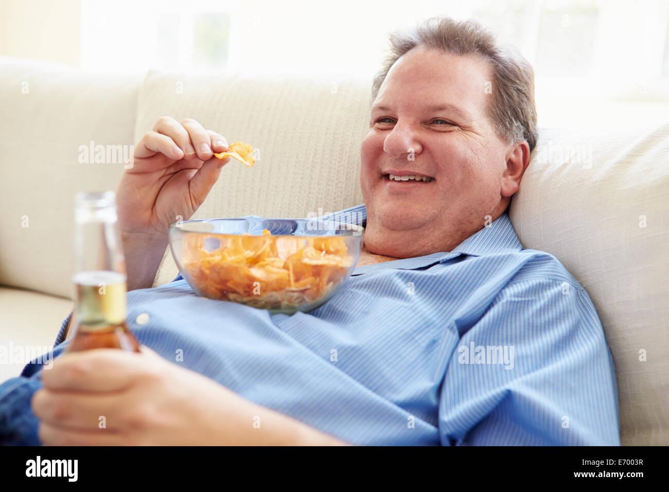 L'excès de Man At Home Eating Chips et boire de la bière Banque D'Images