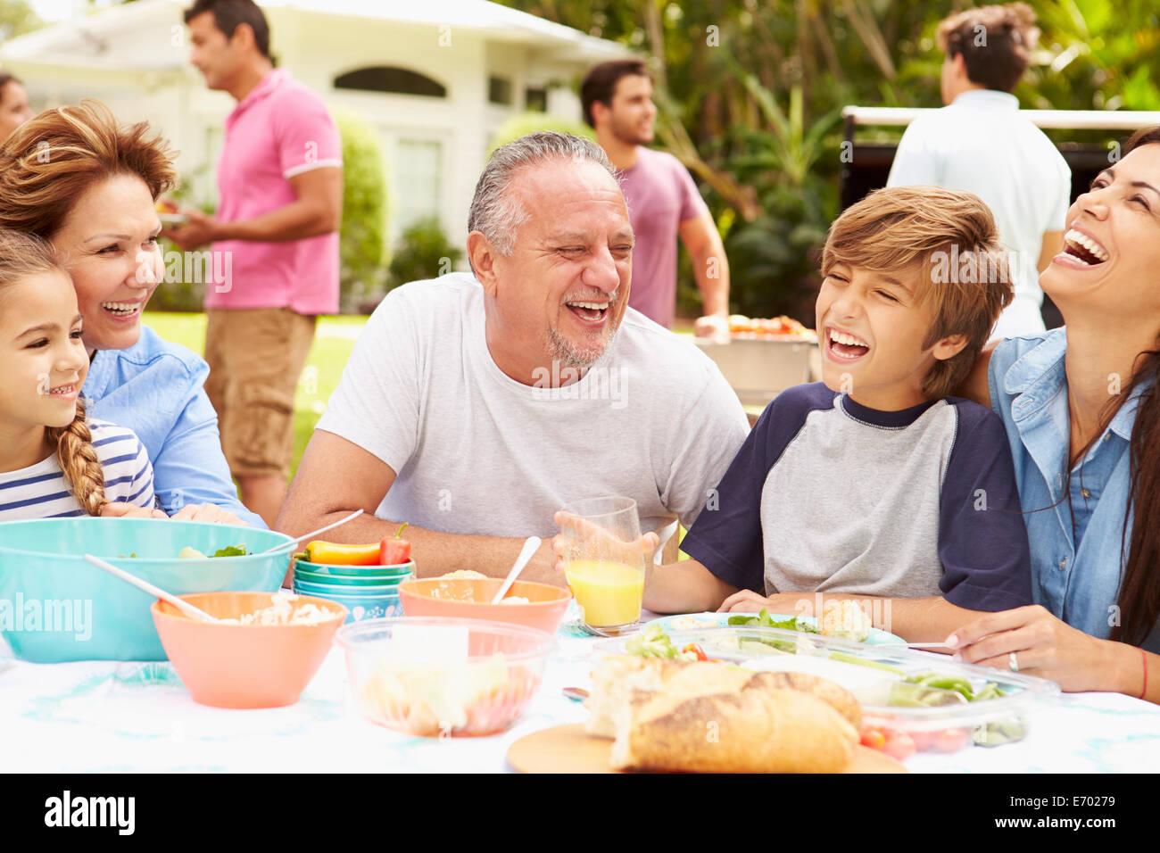 Multi Generation Family Enjoying meal in Garden Ensemble Photo Stock