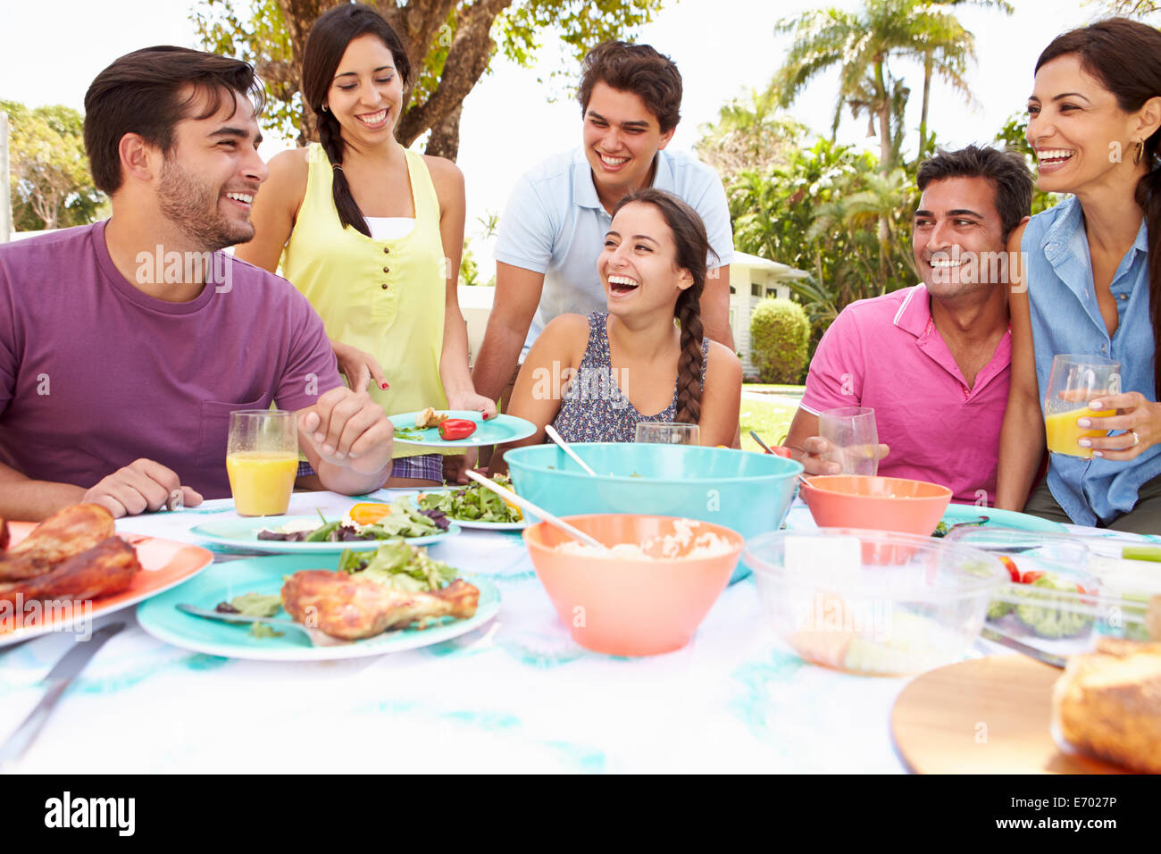 Group of Friends Celebrating Enjoying meal in garden at home Photo Stock