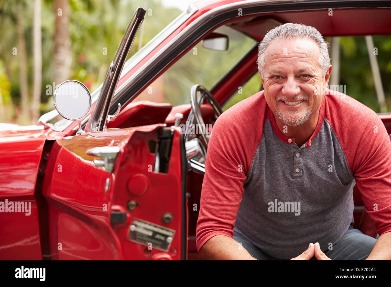 Cadre supérieur retraité homme assis en voiture classique restauré Photo Stock
