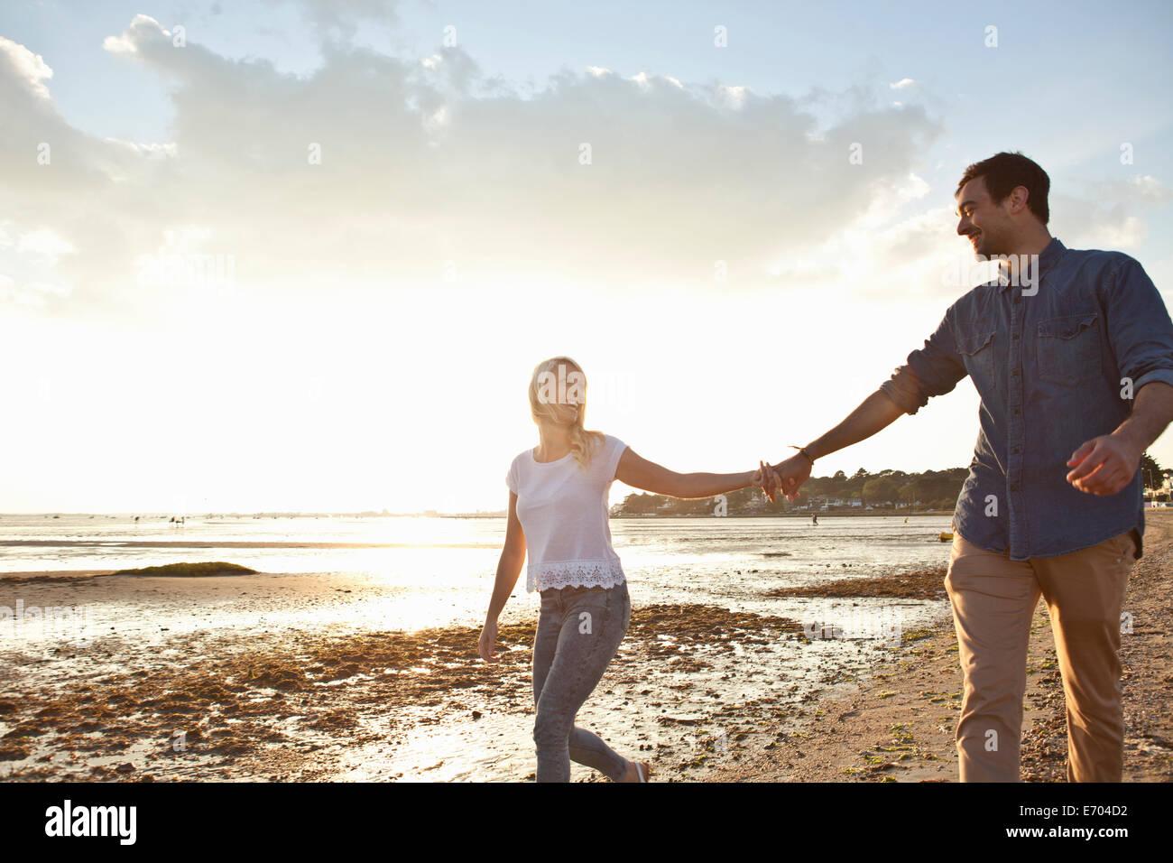 Jeune couple walking on beach Photo Stock