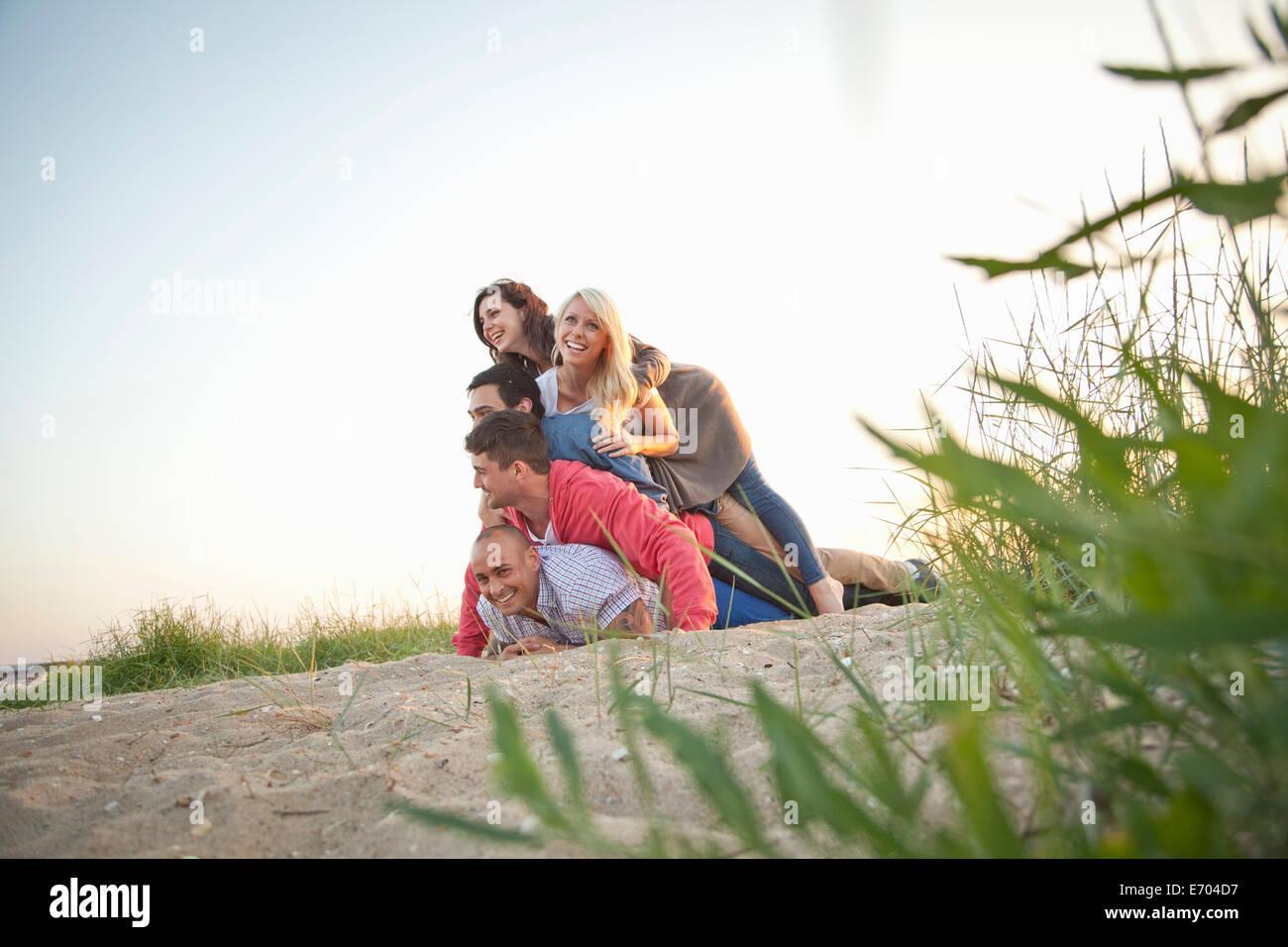 Groupe d'amis faire des droits de l'homme des tas sur beach Banque D'Images