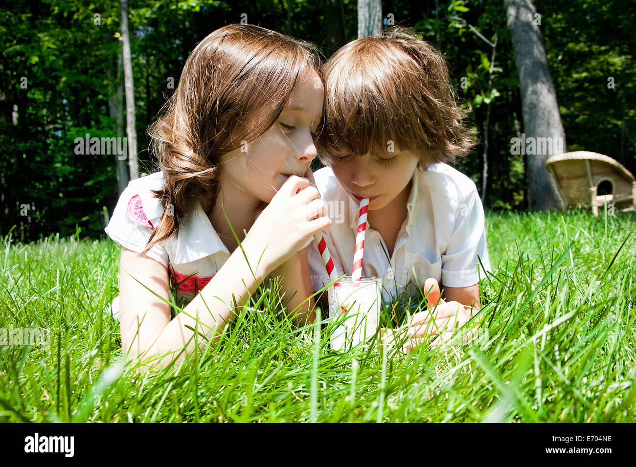Frère et soeur dans les bois le partage d'un milkshake Photo Stock