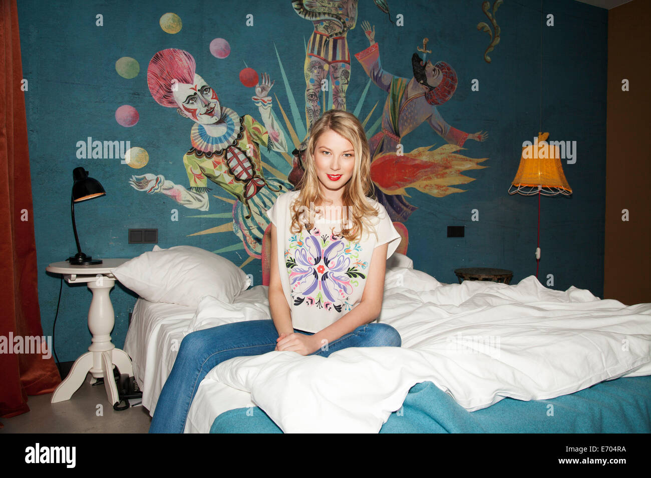 Portrait of young woman sitting on hotel bed Banque D'Images