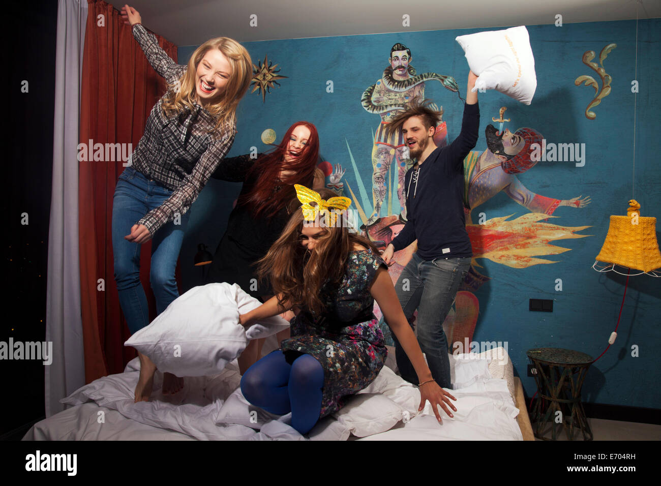 Quatre amis adultes Body Glamour on hotel bed Banque D'Images