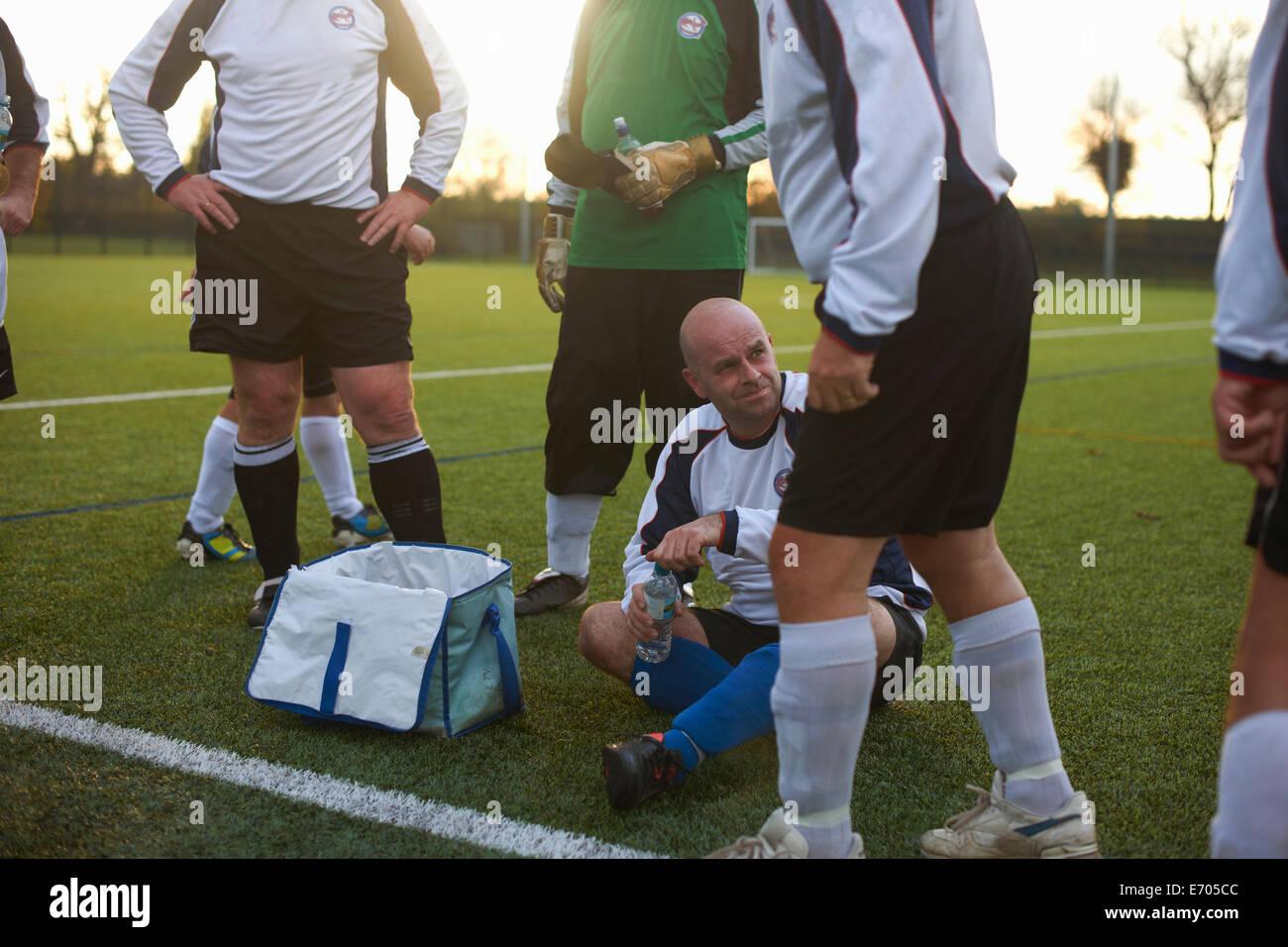 Les joueurs de football et hydratant au repos à la mi-temps Photo Stock