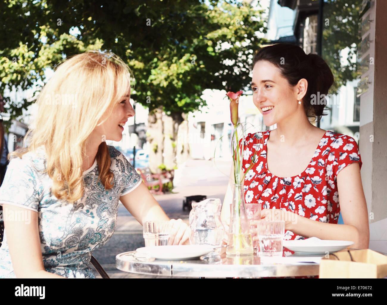 Deux jeunes femmes chatting at sidewalk cafe Banque D'Images