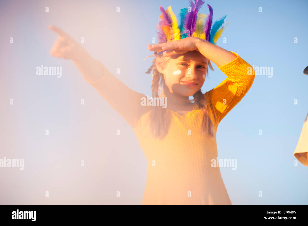 Native American boy coiffure plume en main avec les yeux d'ombre et de pointage Photo Stock