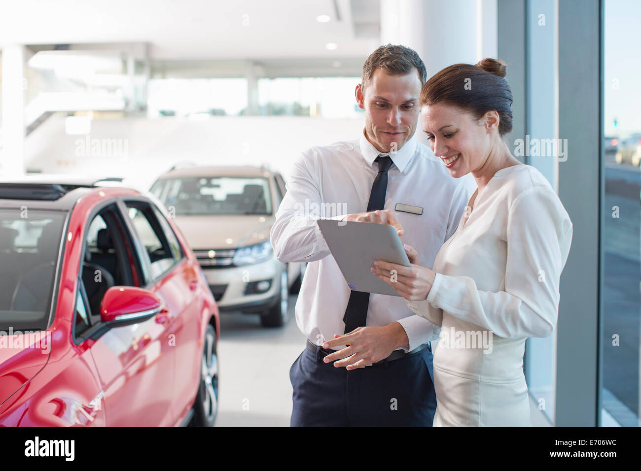 Vendeur et female customer using digital tablet in car dealership Photo Stock