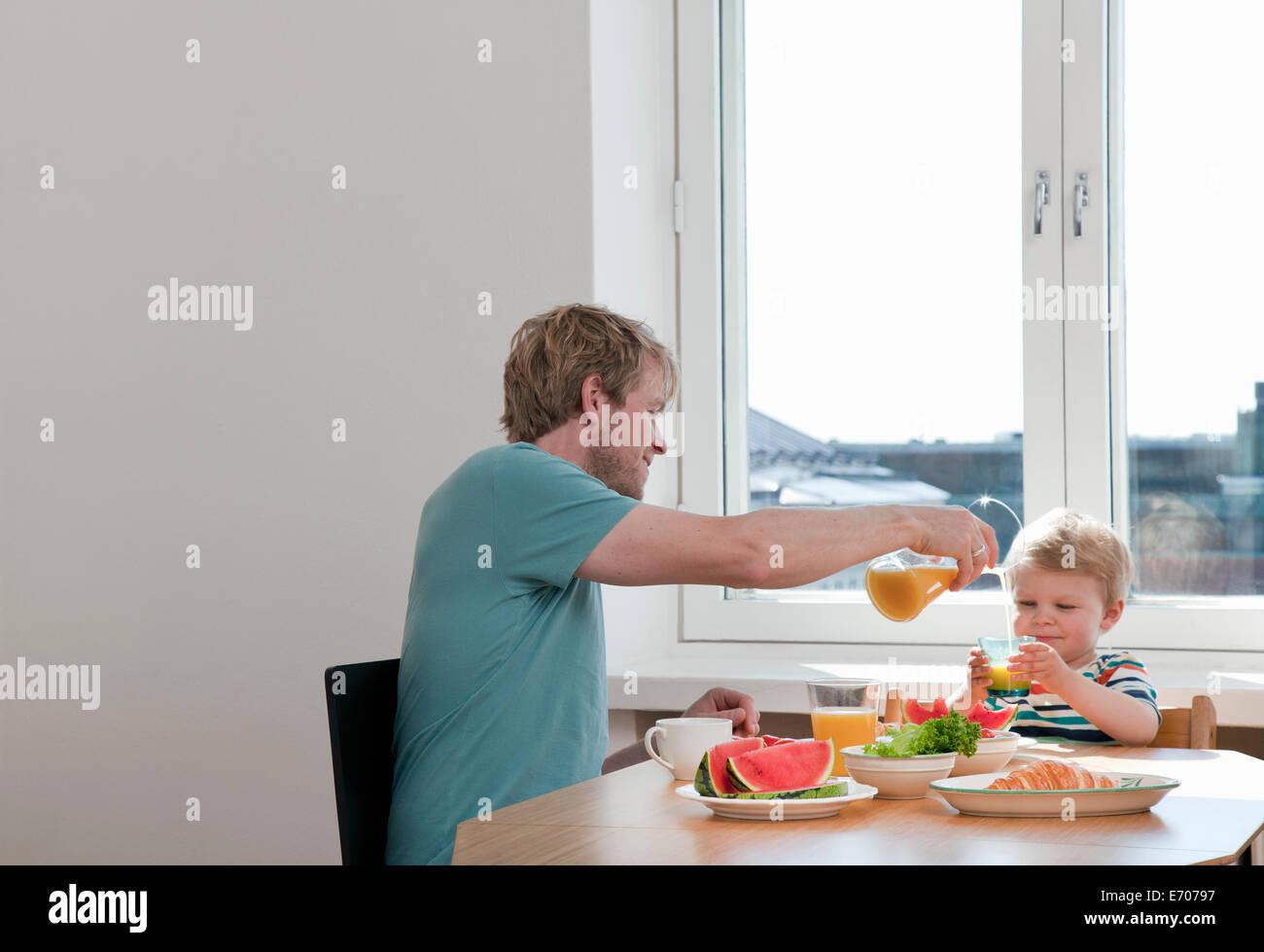 Le père et le petit garçon le petit-déjeuner à table de cuisine Photo Stock
