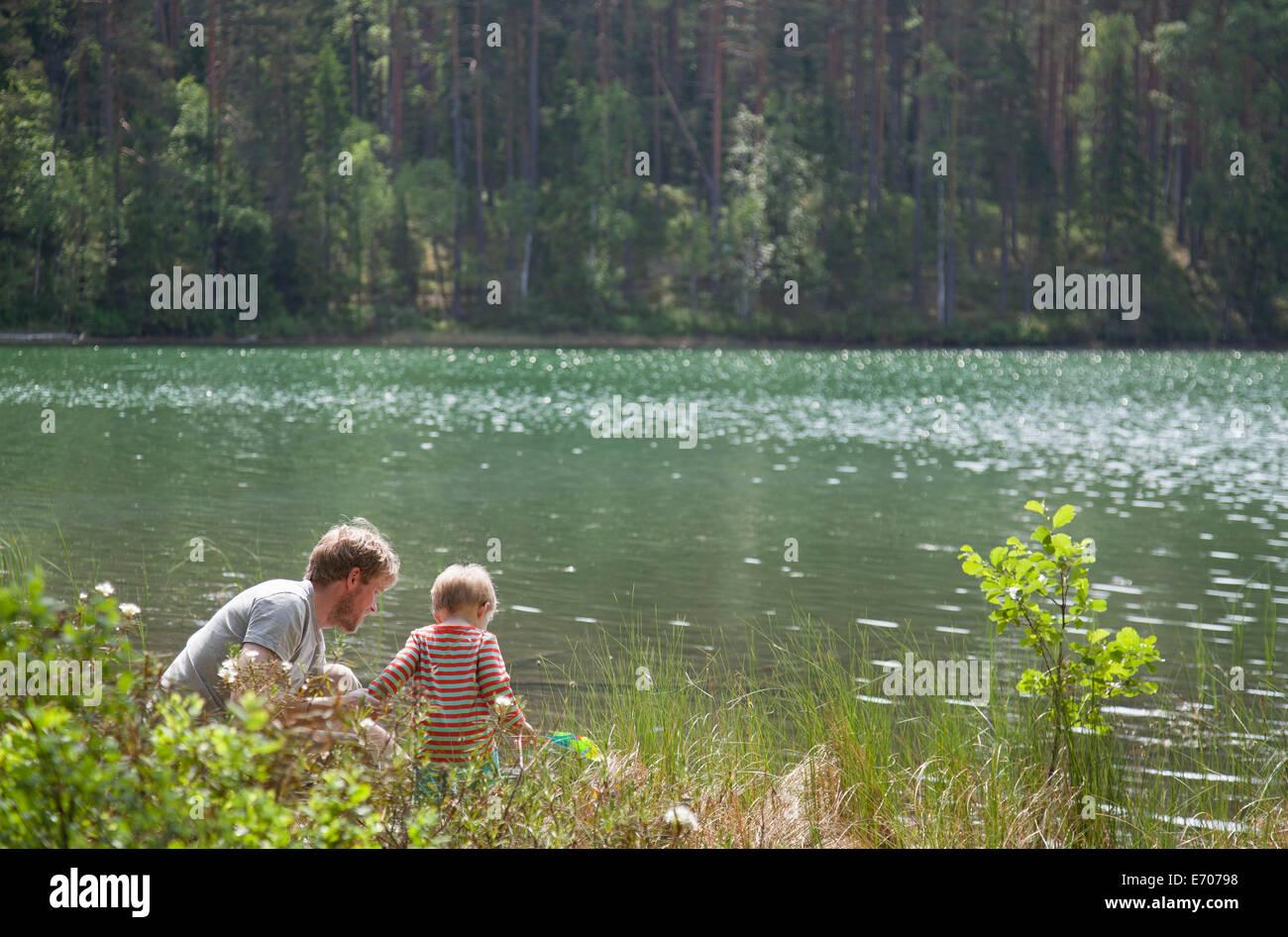 Père et fils à la recherche vers le bas dans le lac, Somerniemi, Finlande Banque D'Images
