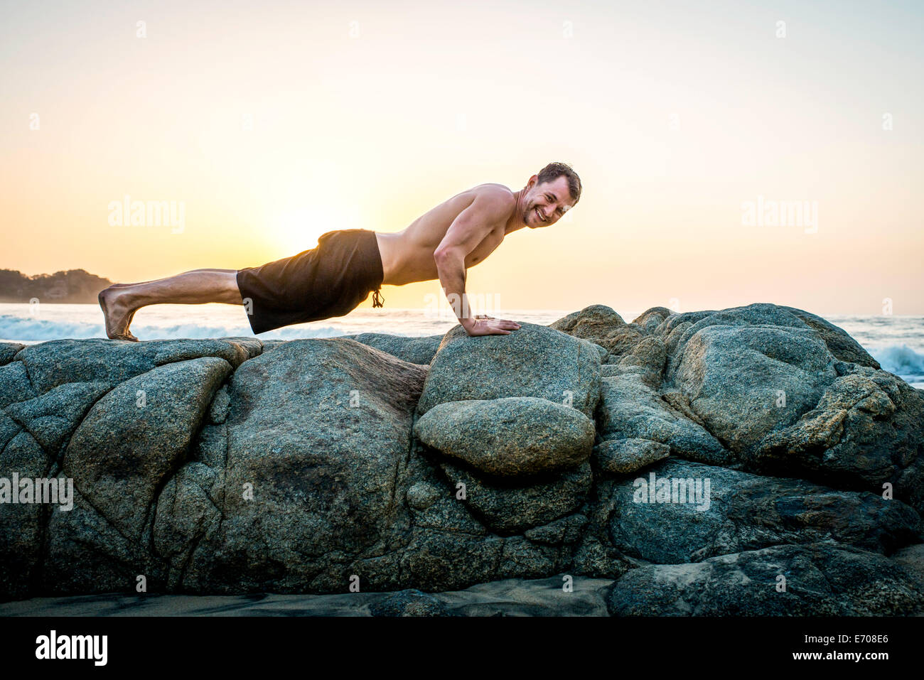 Mid adult man doing push-ups sur des rochers à la plage Photo Stock